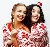 Glückliches Lächeln der Junge recht blond und Brunettefrauenfreundinnen auf Weihnachten in rotem Hut Sankt und Feiertag verziert Lizenzfreies Stockfoto