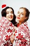 Glückliches Lächeln der Junge recht blond und Brunettefrauenfreundinnen auf Weihnachten in rotem Hut Sankt und Feiertag verziert Stockbilder