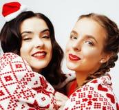 Glückliches Lächeln der Junge recht blond und Brunettefrauenfreundinnen auf Weihnachten in rotem Hut Sankt und Feiertag verziert Lizenzfreie Stockbilder