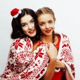 Glückliches Lächeln der Junge recht blond und Brunettefrauenfreundinnen auf Weihnachten in rotem Hut Sankt und Feiertag verziert Lizenzfreies Stockbild