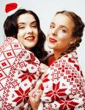 Glückliches Lächeln der Junge recht blond und Brunettefrauenfreundinnen auf Weihnachten in rotem Hut Sankt und Feiertag verziert Stockfotos