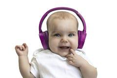 Gl?ckliches L?cheln des Babykindkleinkindes in drahtlose purpurrote Kopfh?rer auf einem wei?en Hintergrund Das Konzept der Techno stockfotografie