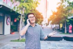 Glückliches Lächeln des jungen asiatischen hübschen Geschäftsmannes beim Ablesen seins Lizenzfreie Stockfotografie