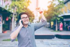 Glückliches Lächeln des jungen asiatischen hübschen Geschäftsmannes beim Ablesen seins Lizenzfreie Stockbilder
