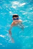 Glückliches Lächeln des kleinen Jungen im Swimmingpool stockfotos