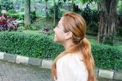 Glückliches, lächelndes asiatisches Mädchengehen im Freien im Park Stockfotos