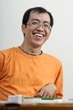 Glückliches lächelndes asiatisches Mannspiel Mahjong Stockbild