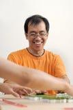 Glückliches lächelndes asiatisches Mannspiel Mahjong Lizenzfreie Stockfotos