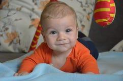 Glückliches lächelndes Baby, das auf seinem Bauch spielt Stockfotografie