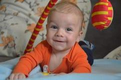 Glückliches lächelndes Baby, das auf seinem Bauch spielt Lizenzfreie Stockbilder