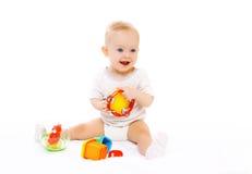 Glückliches lächelndes Baby, das mit Spielwaren auf Weiß spielt Lizenzfreie Stockbilder