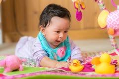 Glückliches lächelndes Baby, das mit Spielwaren spielt Stockbilder