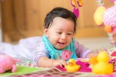 Glückliches lächelndes Baby, das mit Spielwaren spielt Stockfotografie