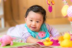 Glückliches lächelndes Baby, das mit Spielwaren spielt Lizenzfreies Stockbild