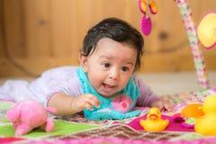 Glückliches lächelndes Baby, das mit Spielwaren spielt Stockfoto