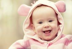 Glückliches lächelndes Baby in der rosa Haube mit den Ohren Stockfoto
