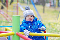Glückliches lächelndes Baby draußen im Herbst auf Spielplatz Stockfotografie