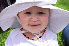 Glückliches lächelndes Baby im weißen Hut Stockfoto
