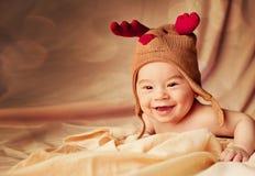 Glückliches lächelndes Baby kleidete im Weihnachtsrotwildhut an stockfotografie