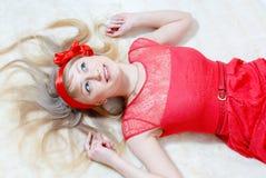 Glückliches lächelndes Bild der schönen lustigen jungen blonden Pinupfrau Stockfotografie
