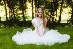Glückliches lächelndes blondes Mädchen, das auf Gras sitzt Lizenzfreies Stockbild