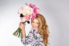 Glückliches lächelndes blondes Mädchen mit Blumenstrauß von Rosen Lizenzfreie Stockbilder