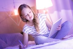 Glückliches lächelndes blondes Mädchenschreiben in ihrem Notizbuch Stockfotografie
