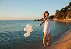 Glückliches lächelndes Brunettemädchen auf sonnigem Strand Stockfoto
