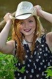 Glückliches lächelndes Cowgirl, das auf ihren Cowboy Hat sich setzt lizenzfreie stockbilder