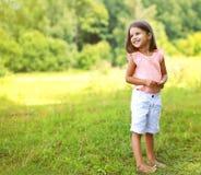 Glückliches lächelndes Genießen des kleinen Mädchens Stockfotos