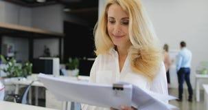 Glückliches lächelndes Geschäftsfrauchefleseberichtsdokument geht von braistorming Sitzung von Geschäftsleuten team herein stock video