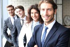 Glückliches lächelndes Geschäftsteam, das in Folge im Büro steht lizenzfreie stockfotografie