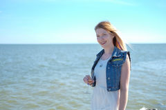 Glückliches lächelndes Hippiemädchen auf dem Seehintergrund Lizenzfreie Stockfotos