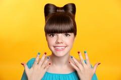 Glückliches lächelndes jugendlich Mädchen mit Bogenfrisur und buntem manicur Lizenzfreie Stockfotografie