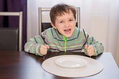 Glückliches lächelndes Jungenkinderwarteabendessen stockbilder