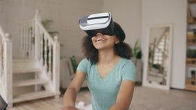 Glückliches lächelndes junges Mischrassemädchen, das Erfahrung unter Verwendung der VR-Kopfhörergläser virtueller Realität und de stock footage