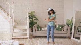 Glückliches lächelndes junges Mischrassemädchen, das Erfahrung unter Verwendung der VR-Kopfhörergläser virtueller Realität erhält stock video footage