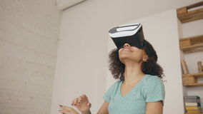 Glückliches lächelndes junges Mischrassemädchen, das Erfahrung unter Verwendung der VR-Kopfhörergläser virtueller Realität und de stock video