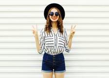 Glückliches lächelndes kühles Mädchen im schwarzen runden Hut, kurze Hosen, weißes gestreiftes Hemd, das auf weißer Wand aufwirft stockfoto