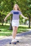 Glückliches lächelndes kaukasisches blondes Jugendlich-Mädchen, das draußen auf Longboard eisläuft Lizenzfreies Stockbild