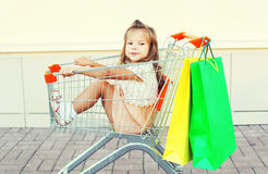 Glückliches lächelndes Kind, das im Laufkatzenwarenkorb mit den Einkaufstaschen haben Spaß sitzt Lizenzfreies Stockbild