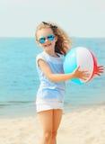 Glückliches lächelndes Kind des kleinen Mädchens, das mit aufblasbarem Wasserball auf Strand nahe Meer spielt Lizenzfreies Stockbild