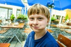 Glückliches lächelndes Kind genießt zu essen Stockfoto