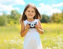 Glückliches lächelndes Kind mit der Retro- Weinlesekamera, die Spaß hat Lizenzfreie Stockfotografie