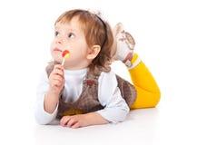 Glückliches lächelndes Kind mit Süßigkeit Stockfoto
