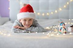 Glückliches lächelndes Kind in Santa Claus-Hut, der im Bett am Weihnachten liegt stockbild
