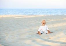 Glückliches lächelndes kleines Kind, das auf dem sonnigen Strand sitzt Lizenzfreie Stockfotografie