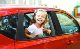 Glückliches lächelndes kleines Kind des Porträts, das im roten Auto sitzt Lizenzfreie Stockfotografie