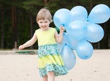 Glückliches lächelndes kleines Mädchen, das mit Ballonen läuft Stockbild