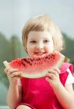 Glückliches lächelndes kleines Mädchen, das Wassermelone isst Lizenzfreie Stockfotografie